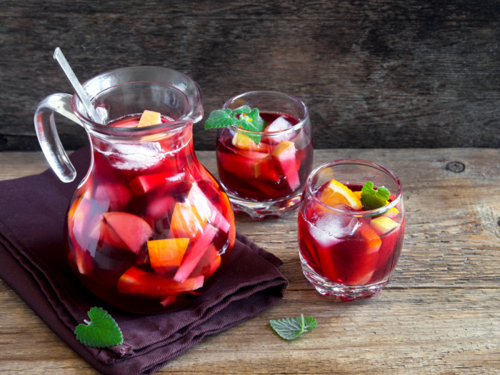 A pitcher and two glasses of red wine sangria with sliced fruits and mint
