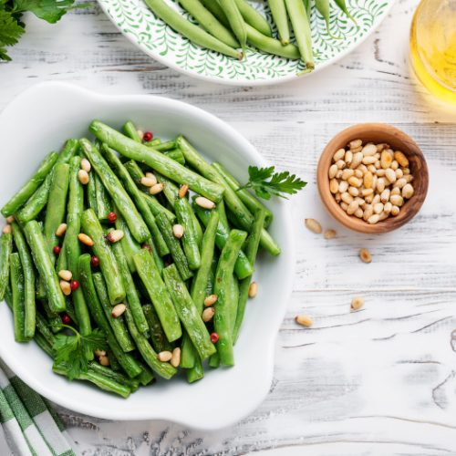 A flat lay picture of sauteed green beans in a white bowl kept atop a white platform