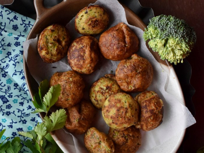 Flatline view of a tray of muffins with a broccoli head and coriander leaves kept on either side