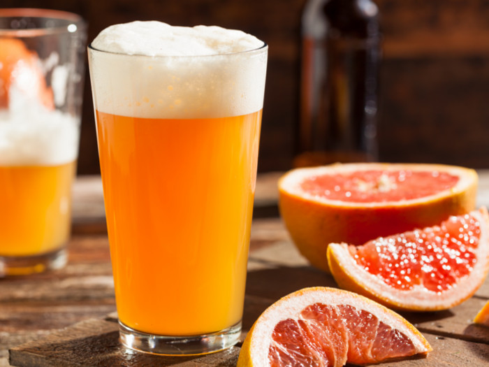 Shandy in a beer glass and grapefruit slices on a counter