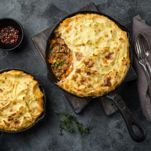 shepherd's pie made of minced meat, mashed potatoes and vegetables casserole in cast iron pan