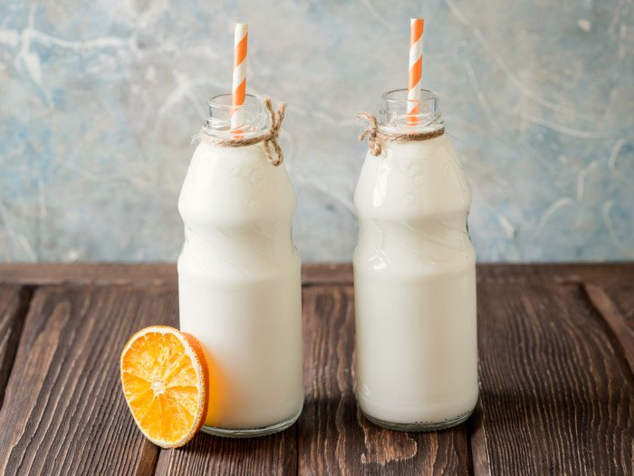 2 bottles fresh skimmed milk with orange striped straws and a slice of lime kept on a wooden table
