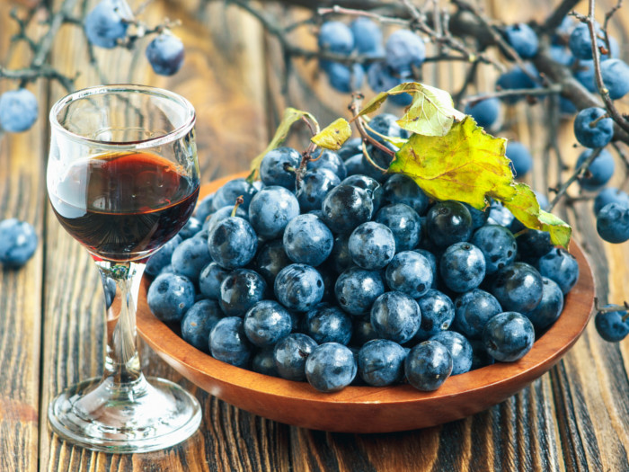 A glass of slow gin kept next to sloe berries atop a table