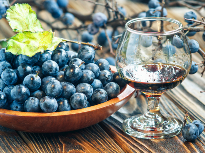 A glass of sloe gin kept next to a bowl of sloe berries kept atop a wooden table