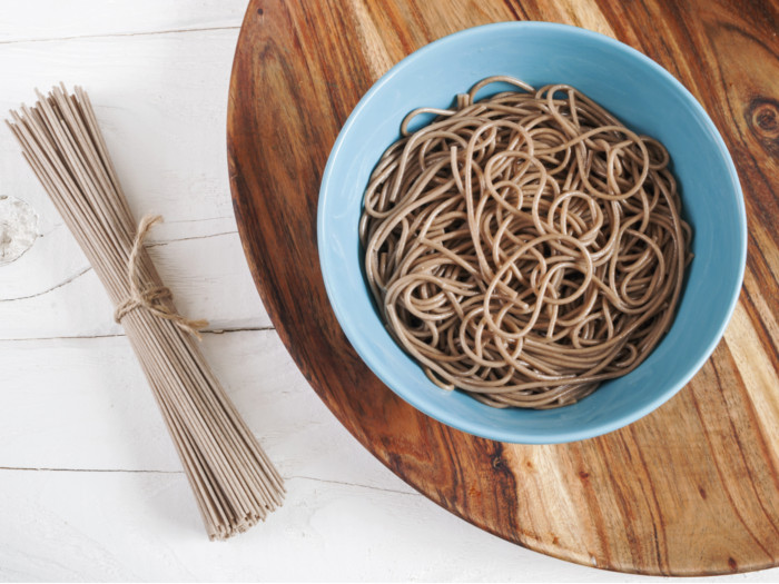 Cooked soba noodles in a bowl and dried soba noodles tied in twine