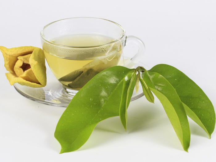 a cup of soursop tea with its leaves aside
