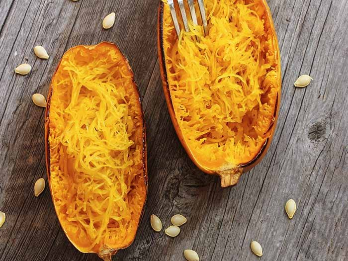 Spaghetti squash placed on a wooden background with seeds