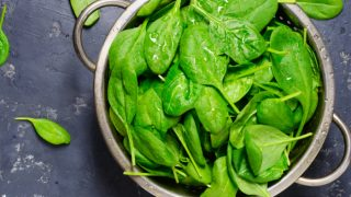 A bowl of spinach leaves on a gray background