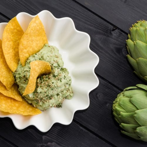Homemade dip with corn nachos and artichokes on the black wooden background