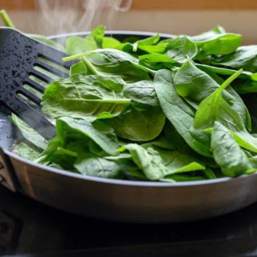 Cooking fresh spinach in a pan on the stove