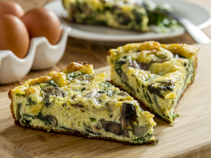 2 slices of spinach mushroom and egg frittata sitting on wooden cutting board