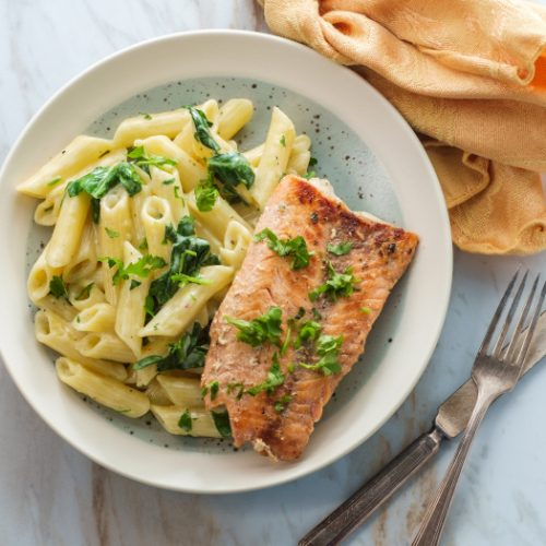 Italian fried salmon and penne pasta with creamy spinach alfredo pasta sauce