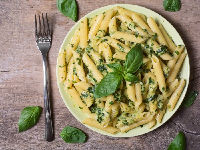 Penne pasta with spinach pesto sauce and green basil on a plate