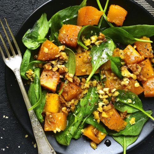 Roasted pumpkin salad with spinach and walnut on a black plate