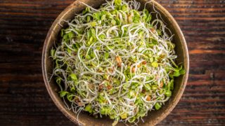 A wooden bowl of fresh sprouts on a wooden table