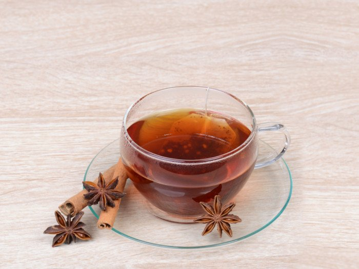 Star Anise Tea kept atop a wooden platform next to star anise and cinnamon sticks