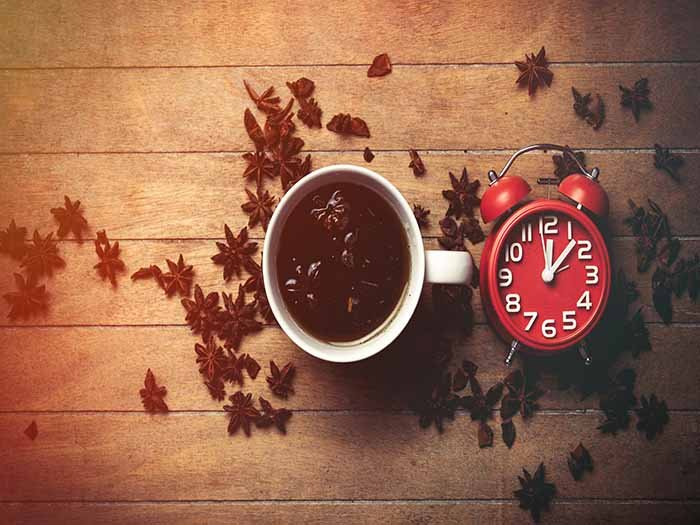 A flat-lay picture of star anise tea surrounded by star anise spices and a red table clock