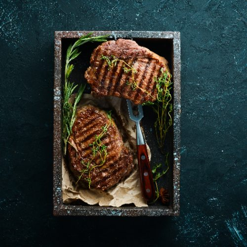 Steak fillets with rosemary and other herbs on a black serving dish on a counter