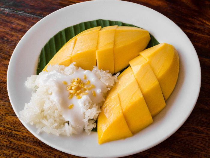 Mango, coconut meat, and sticky rice on a banana leaf on a white dish