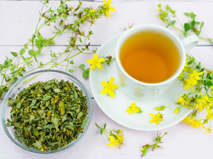A cup of St John's wort tea kept next to a bowl of St. John's wort herb