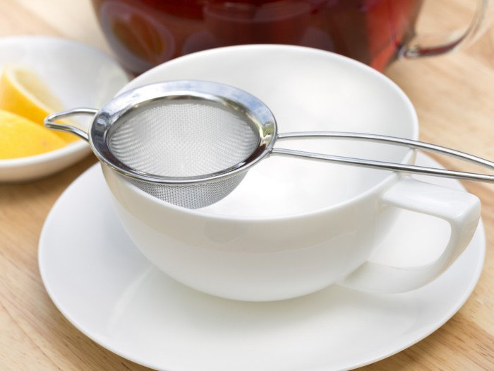 A teacup with a tea strainer and lemon slices in the background