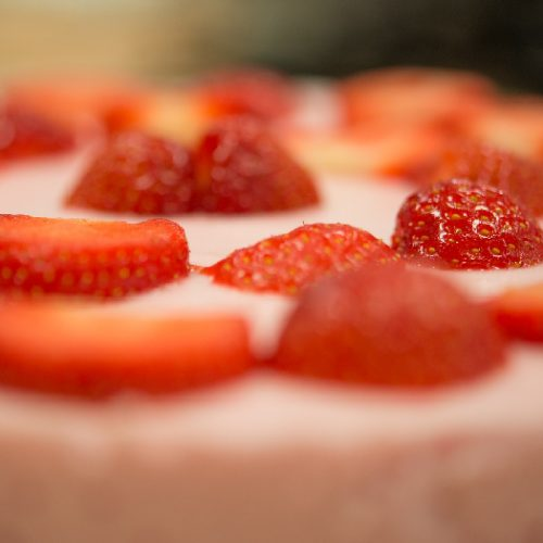 Extreme close-up of strawberries in cream.