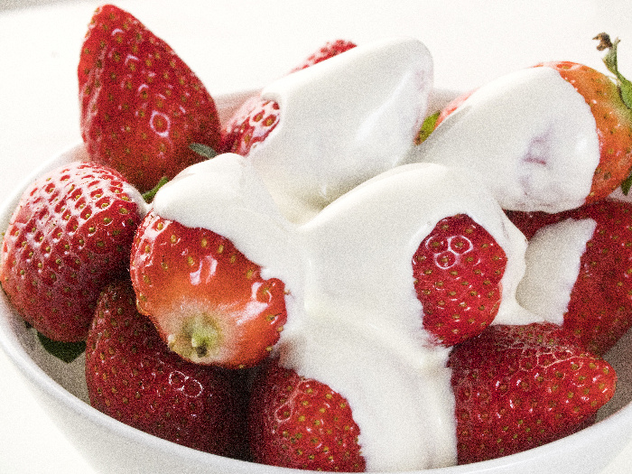 A bowlful of strawberries and cream against a white background