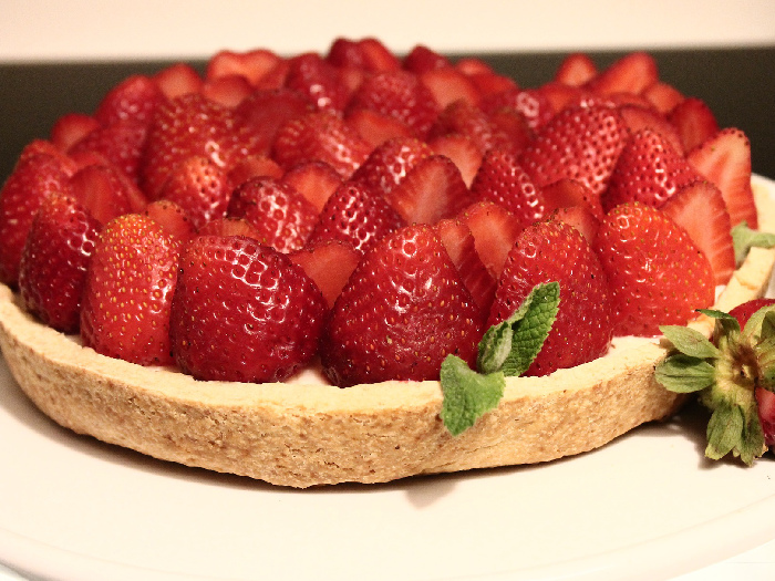 A Cream Pie covered with strawberries