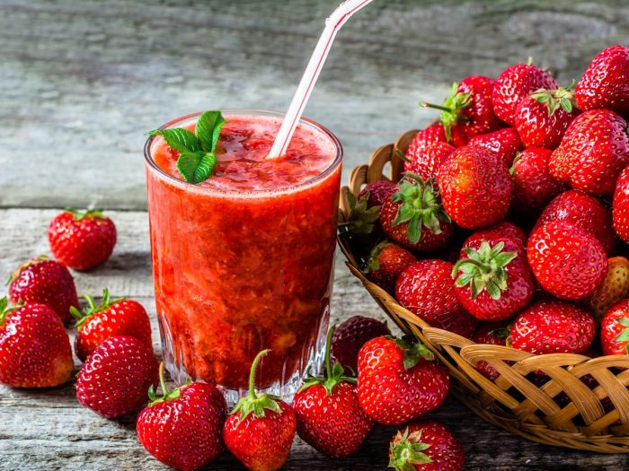 A glass of fresh strawberry juice kept beside a basket of juicy strawberries