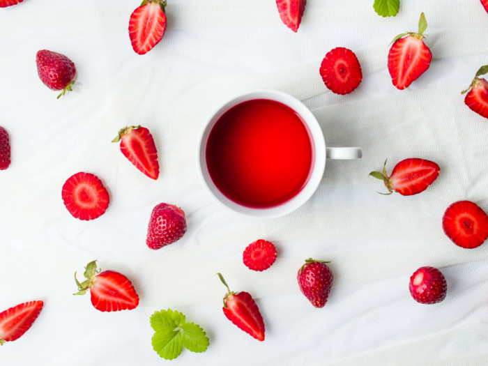 A cup of strawberry tea, whole and sliced strawberries on a white counter.