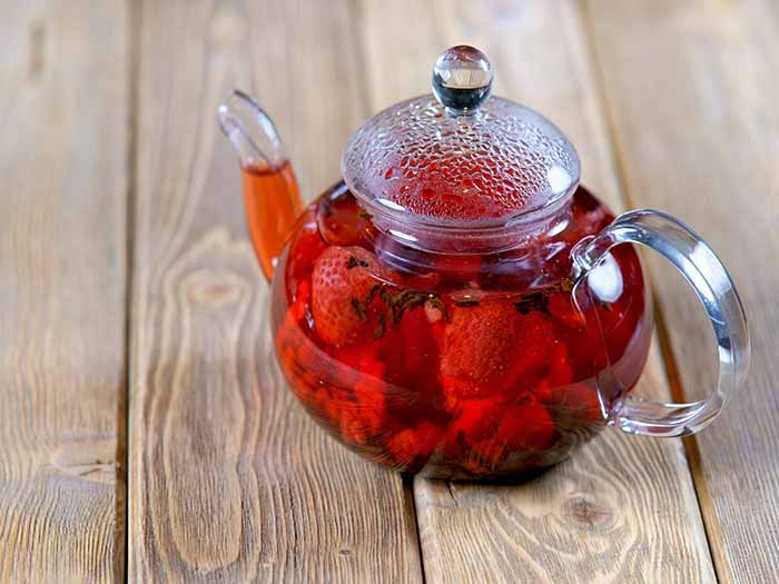 A glass teapot with cut strawberries and whole spices on a wooden counter