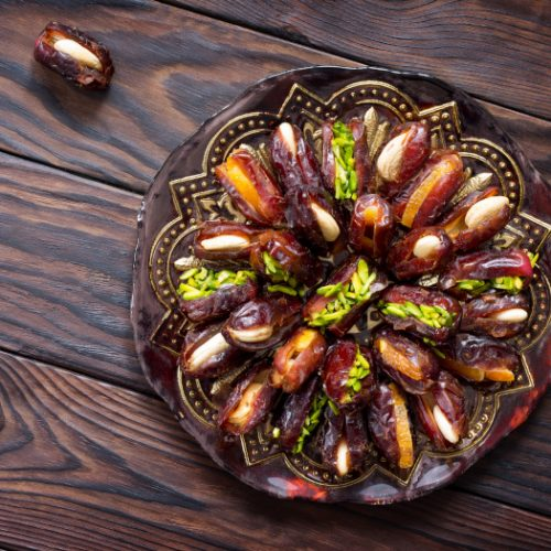 A plate with stuffed dates on a wooden table