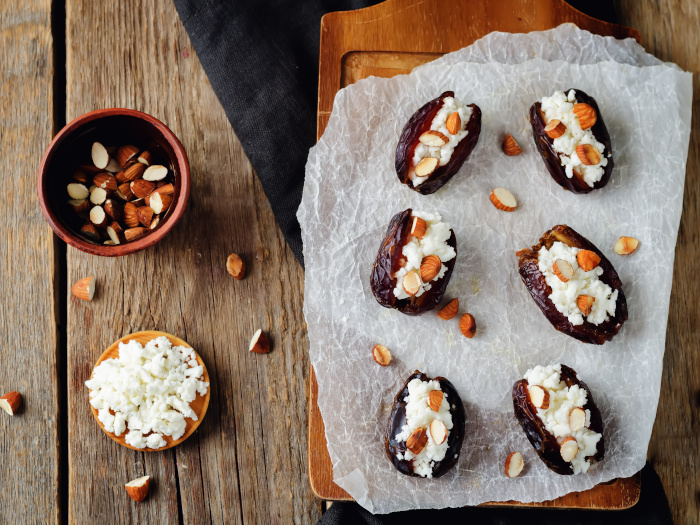 Almond and goat cheese stuffed dates on a wooden cutting board