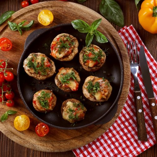 A flat lay image of a frying pan with stuffed mushrooms and vegetables on the table
