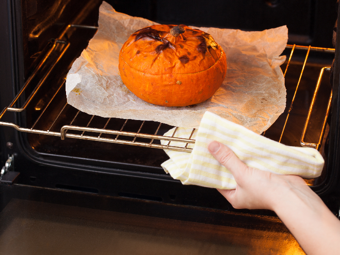 The process of cooking pumpkin in the oven. Baked pumpkin with mushrooms and barley in the oven.