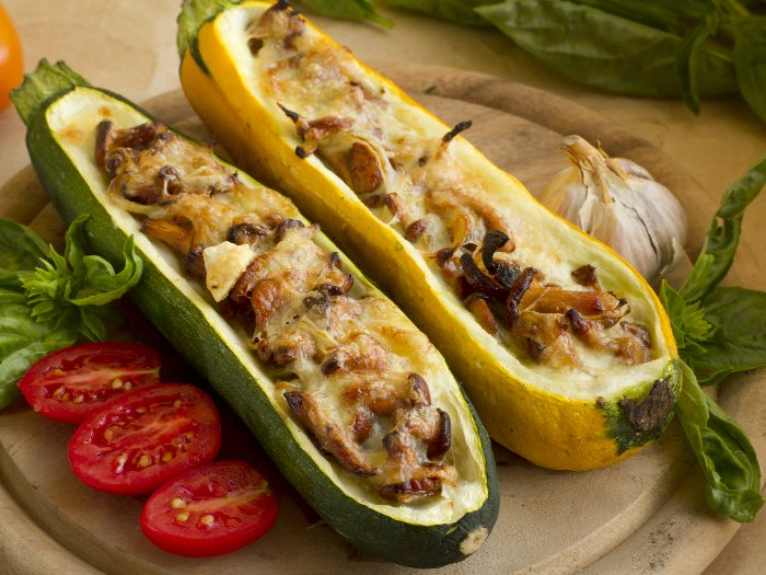 Stuffed zucchini with mushrooms and cheese on a wooden plate