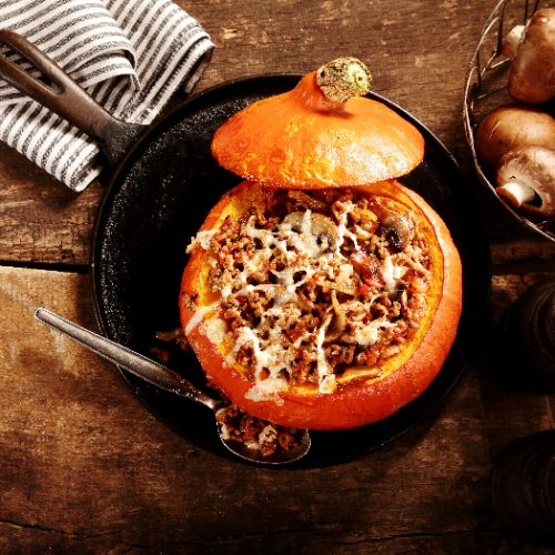 A flatlay picture of tasty autumn stuffed pumpkin with fresh mushrooms ready to serve for a seasonal dinner,