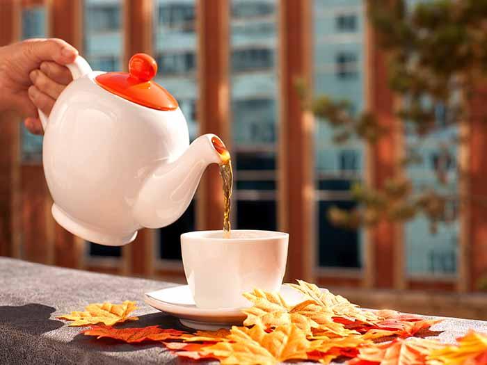 Pouring tea through a kettle into a cup