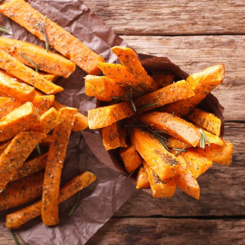 Sweet potato fries with ketchup on parchment paper and wood
