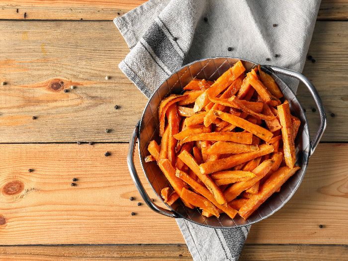 Sweet potato fries in a bowl on a napkin on a wooden table