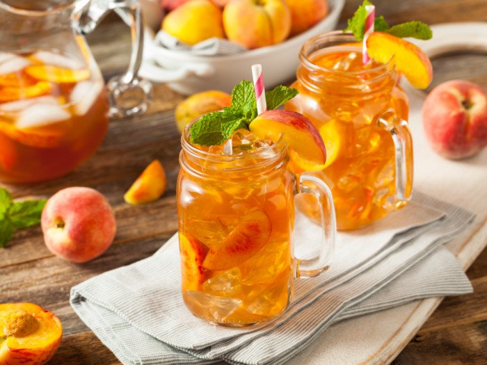 Sweet tea flavored with fresh peach in mason jars and a pitcher, with peaches on a table