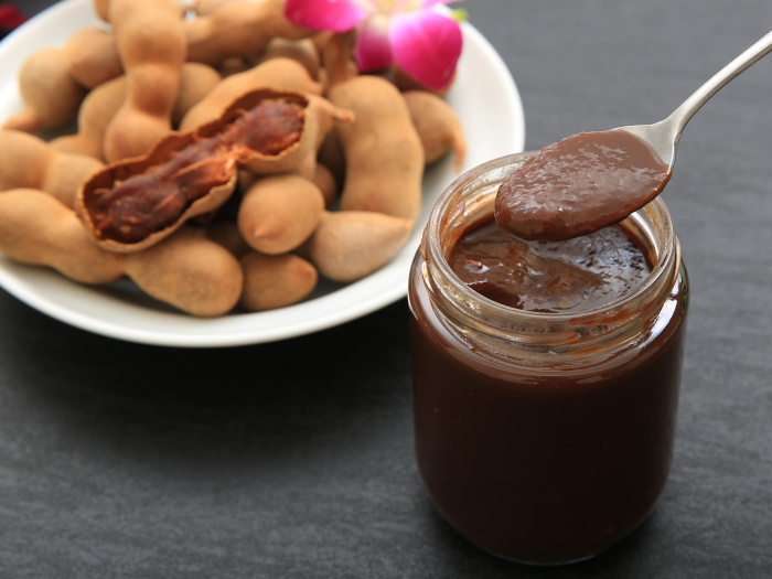 Tamarind chutney in a jar with a spoon next to a plate of whole tamarind