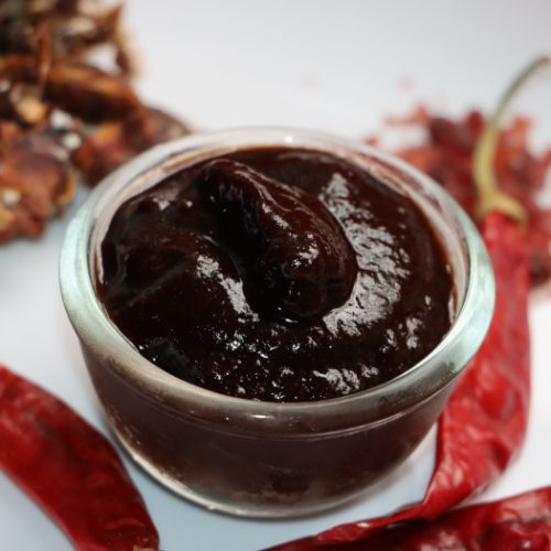 A small bowl of tamarind chutney on a white plate with scattered red chillies and tamarind