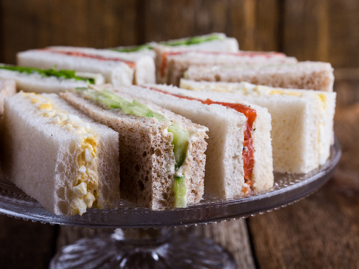 English tea sandwiches on a cake stand over rustic wooden background
