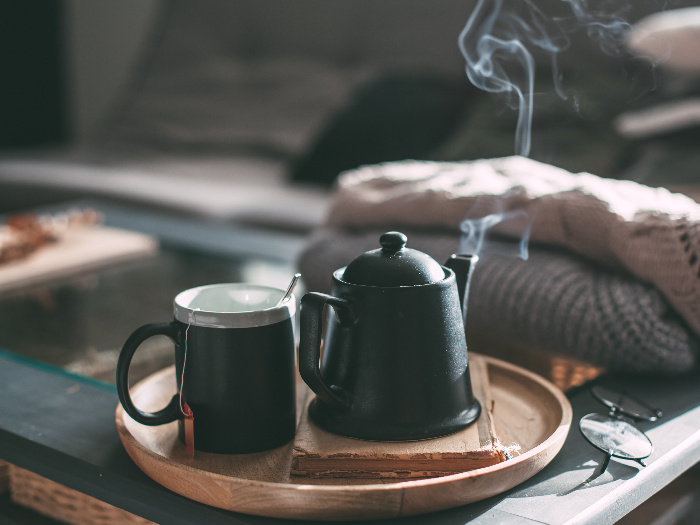 A steaming cup of tea and a pot on a table
