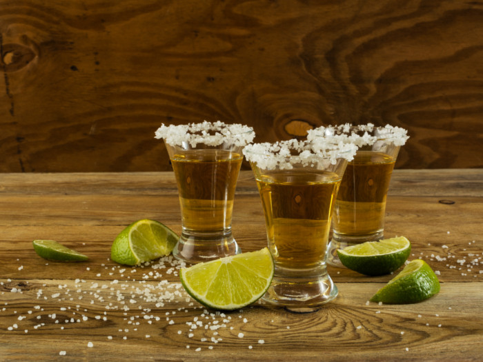 Three tequila glasses kept atop a wooden table with lemon slices cut and kept next to the glasses