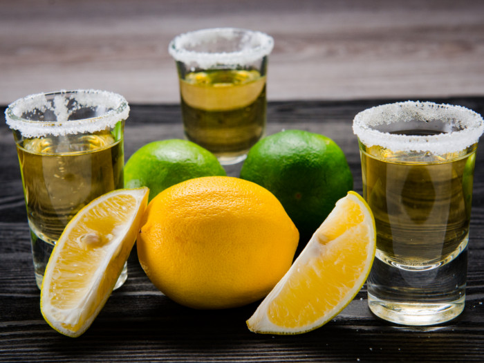 Tequila in shot glasses with salted rims, with limes and lemons on the side