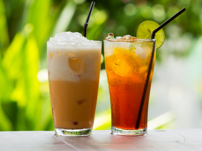 Two glasses of iced tea next to each against a green background