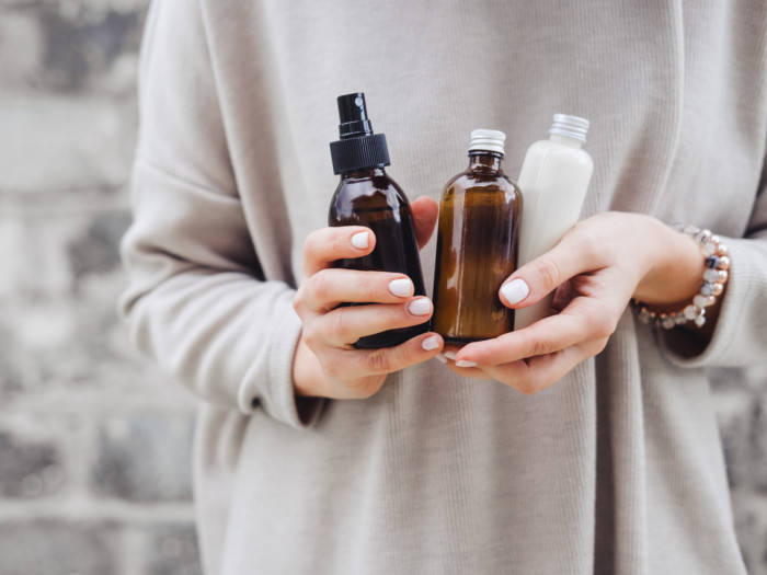 A woman holding 3 bottles of essential oil