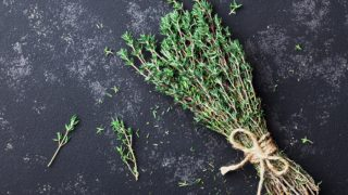 A bunch of fresh thyme herb on a black background